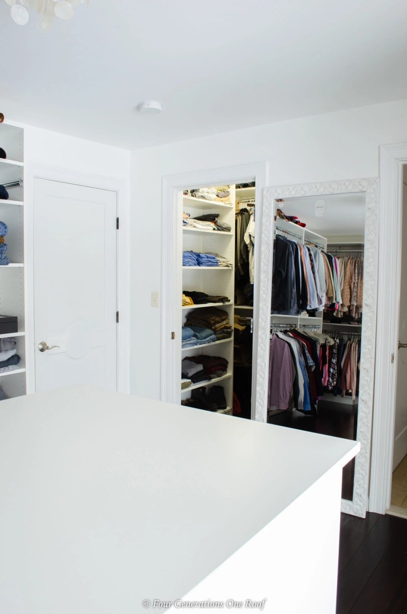 walk in closet with white wood shelving and hanger system, center island