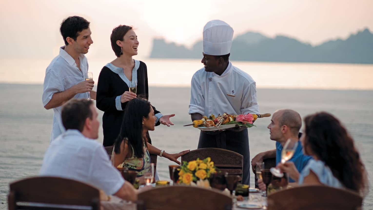 Chef presents platter of grilled meats to group of friends at beach dining table
