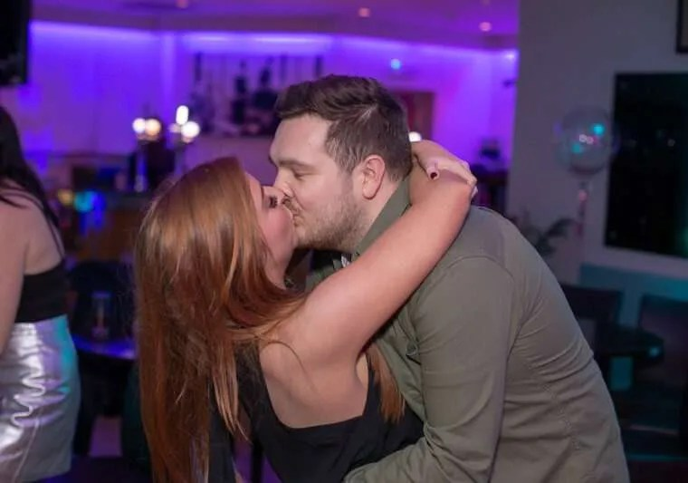 A couple kissing at a party