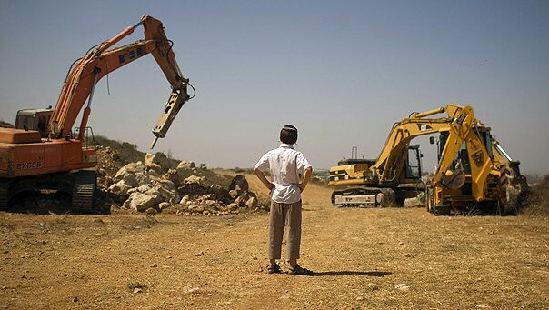 Sept. 27: A young Jewish settler looks at earth-moving equipment at a construction site in the West Bank.