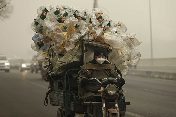 Person wearing a paper breathing mask while driving in a smoggy area