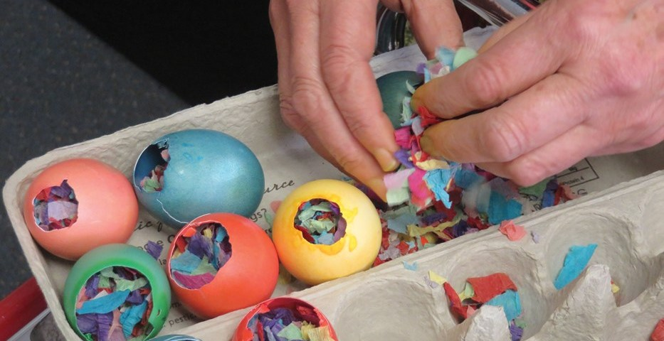 colored eggs in an egg carton with hands filling them with colorful scraps