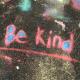 multicolord chalk art on asphalt that says Be Kind