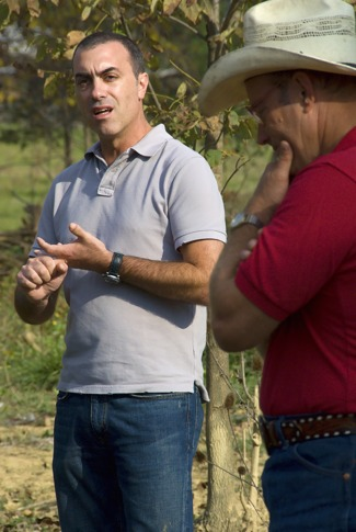 Joel Salatin (right) ponders as Phil Petrelli of Chipotle talks to SEJ members at PolyFace Farms, Oct 2008.