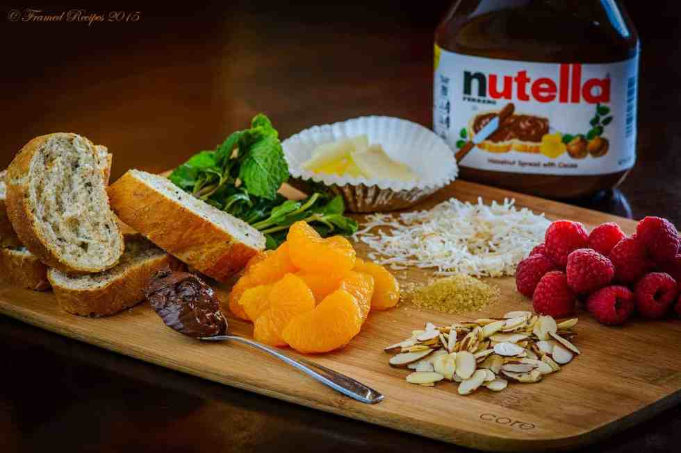 ingredients to make the nutella bruschetta - bauguette, nutella, butter, mint leaves, almonds, raspberries and mandarin oranges.
