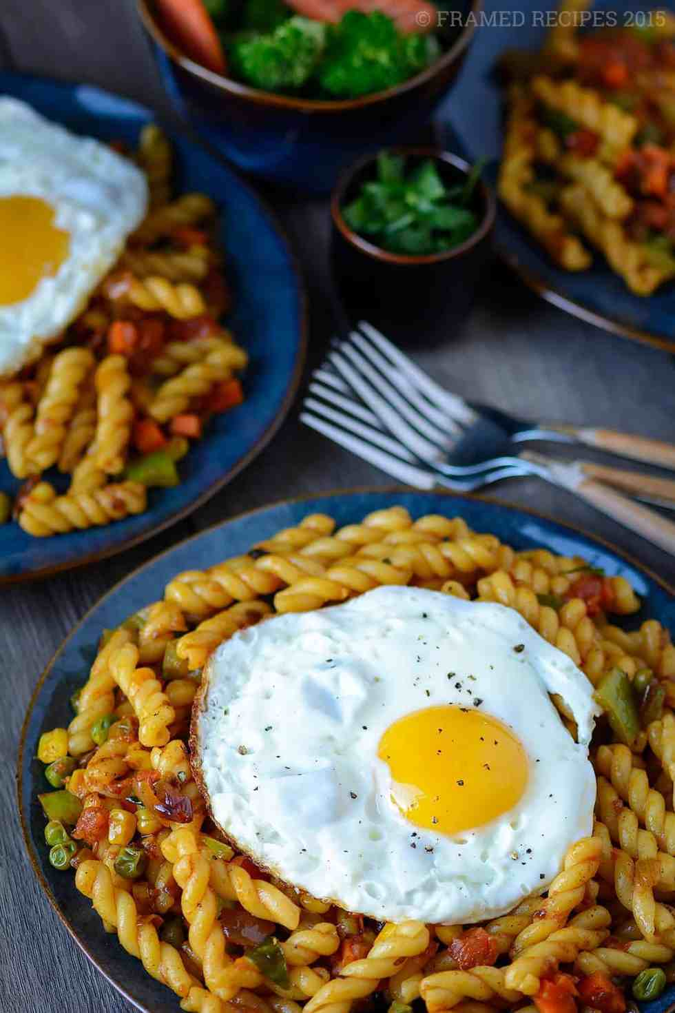 fusion pasta recipe - pasta with Indian flavors topped with  over-easy eggs and a side of steamed broccoli and carrots.