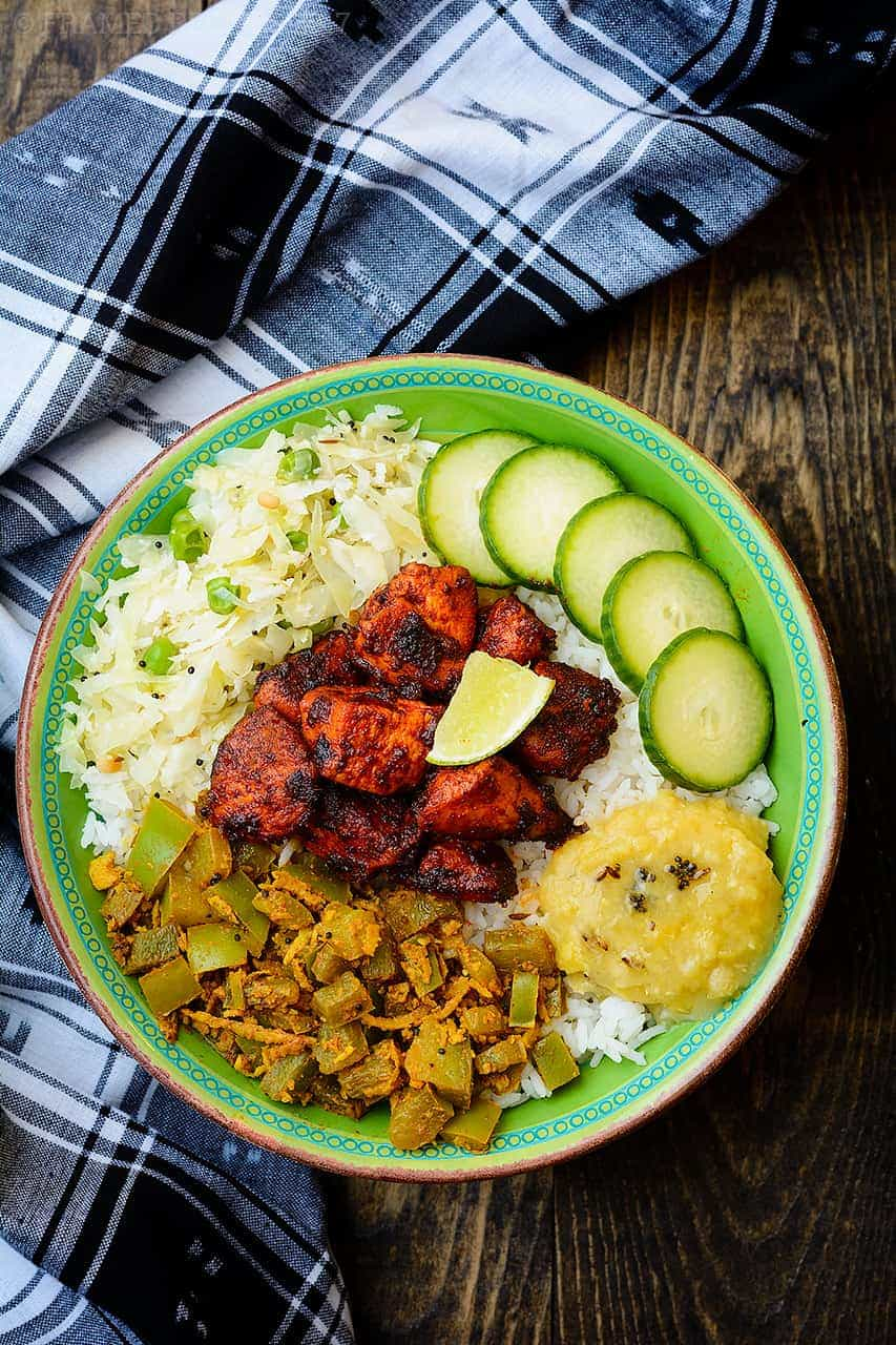 Chicken Ghee Roast served with rice, cabbage thoran, bell pepper stir fry, dali thoy and steamed rice.