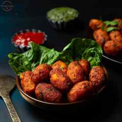 Cauliflower tots in a brown bowl with lettuce leaf as garnish