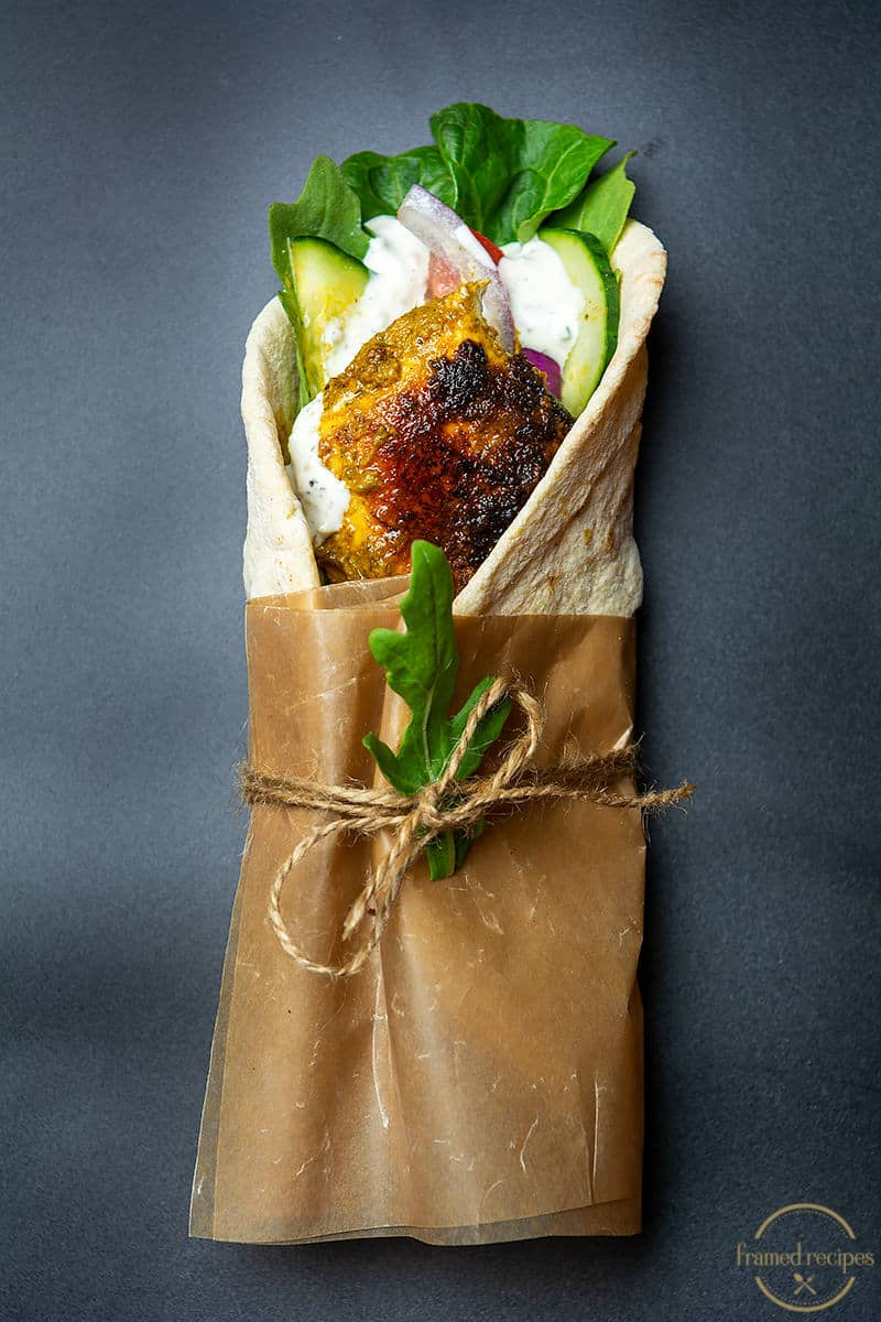 green chutney chicken wrap with lettuce leaves, sliced cucumbers and onions drizzled with  tzatziki sauce.