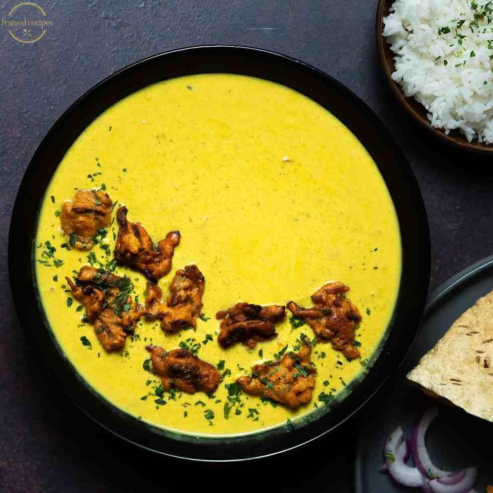 ready to serve - kadhi pakora with rice, papad, onion.