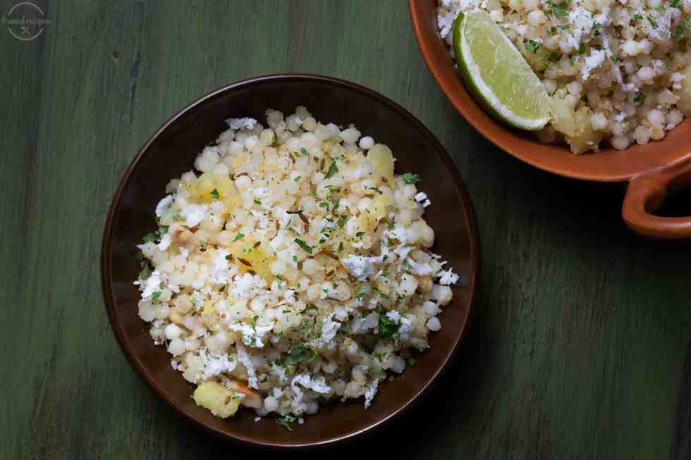 sabudana cooked with spices, peanuts and potatoes garnished with coconut and cilantro served with lemon wedges.