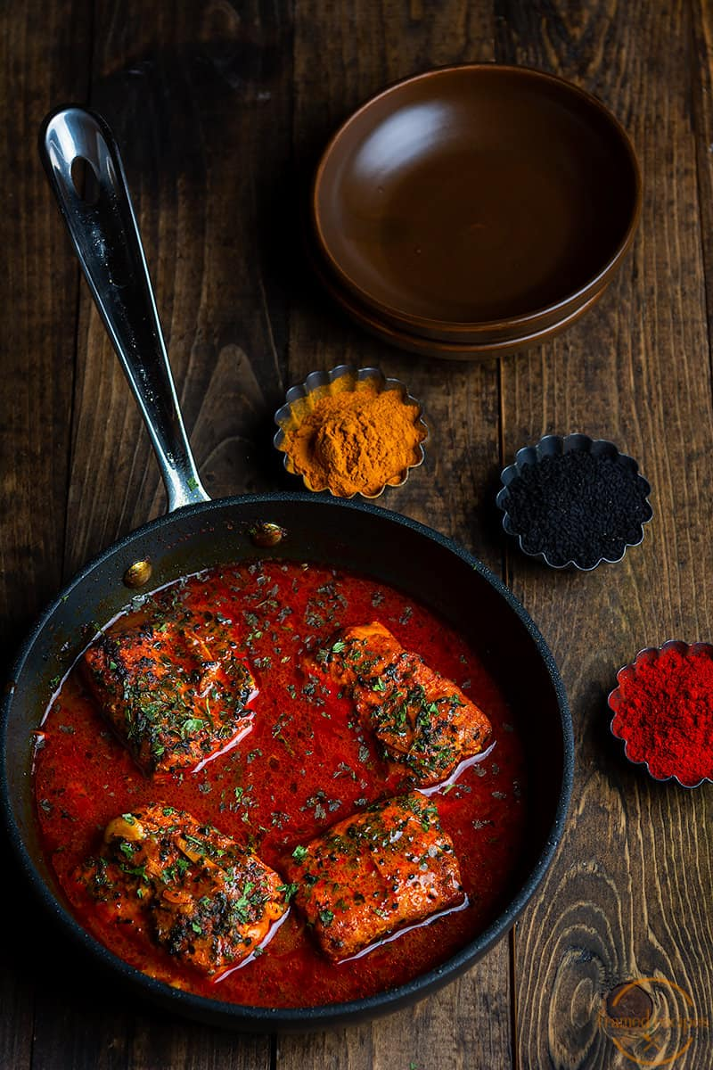 Bengali style fish curry shown with a few of the spices used in preparation - turmeric powder, nigella seeds, kashmiri red chilli powder - along with two empty serving dishes
