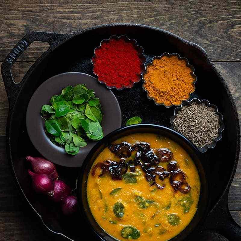muringa ila curry shown with pearl onions, raw moringa leaves, red chili powder, turmeric and cumin seeds