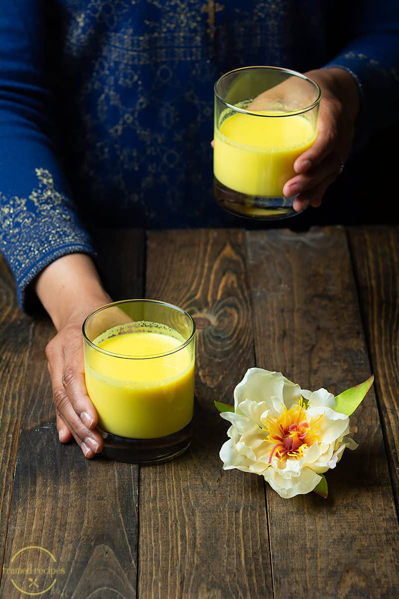 lady holding a glass of warm turmeric latte
