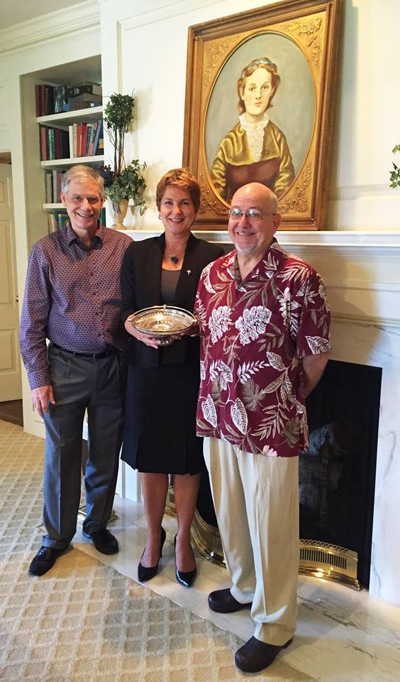 The family of Carole Cones-Bradfield, great granddaughter of Bettie Locke Hamilton, stopped by for a tour. Carole recently passed away, and she generously donated many items to the Theta archive that belonged to her great-grandmother. CEO Betsy Corridan is pictured holding Bettie's famous Theta cake basket. On the left is Dane Hartley, great-grandson of Bettie Locke, a DePauw alumnus, and a Phi Gamma Delta. He was Carole Cones-Bradfield's cousin. On the right is Landis Bradfield, Carole's husband.