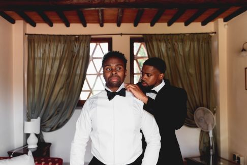The best man helps the groom in wearing the papillon | Villa la palagina resort