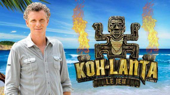 """Le présentateur de l'émission, Denis Brogniart, pose devant lelogo de l'émission """"Koh-Lanta""""."""