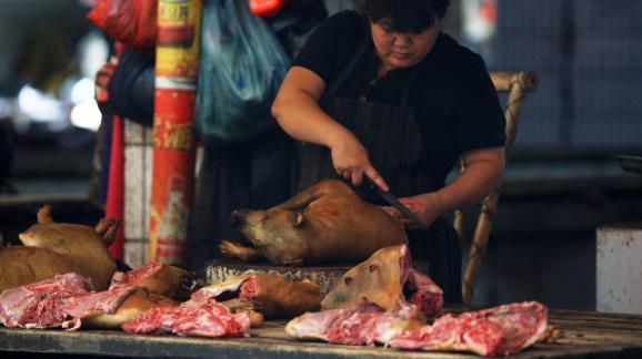 Une femme coupe de la viande de chien disponible à la vente sur le marché de Yulin (Chine), le 18 juin 2014.