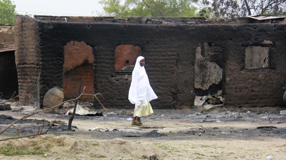 A Baga, une femme passe devant des maisons brûlées après une attaque en avril 2013. Boko Haram a à nouveau attaqué cette ville en janvier 2015, tuant des centaines, voire des milliers, de personnes.