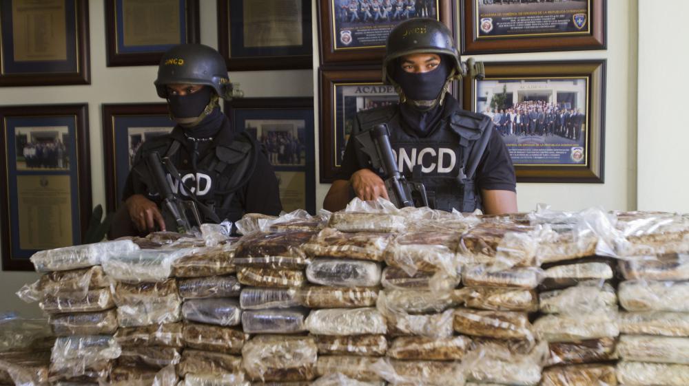 Des policiers dominicains posent devant les 680 kg de cocaïne saisie à bord du Falcon 50 des quatre Français, le 21 mars 2013.