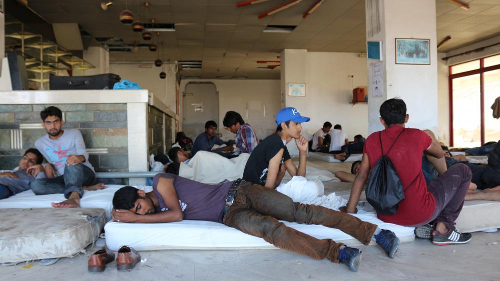 Des migrants se reposent devant l'ancienne réception de l'hôtel Captain Elias, le 19 août 2015 à Kos (Grèce).
