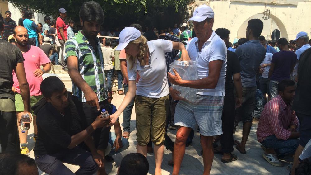 Des touristes hollandais distribuent des bouteilles d'eau aux migrants qui attendent devant le poste de police de Kos (Grèce), le 20 août 2015.