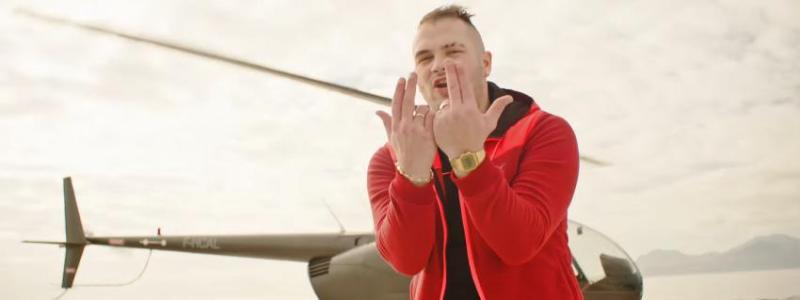 """Le rappeur Jul, qui sort un nouvel album vendredi 2 décembre 2016, exécute son signe icônique dans le clip de \""""Comme d\'hab\""""."""