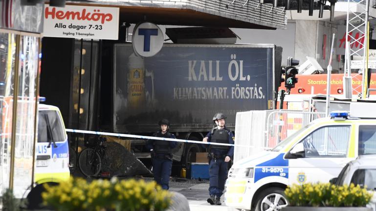 La police suédoise dresse un cordon de sécurité autour du camion qui a renversé des piétons avant de s\'encastrer dans une magasin, à Stockholm, vendredi 7 avril 2017.