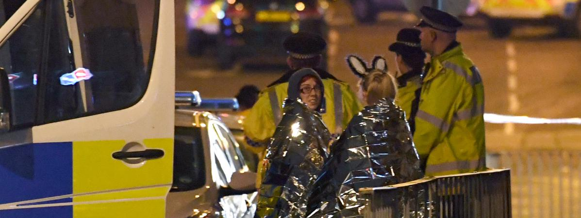 Des spectactrices présentes au concert d\'Ariana Grande sont prises en charge par les secours, dans la nuit du 22 mai 2017, à Manchester (Royaume-Uni).