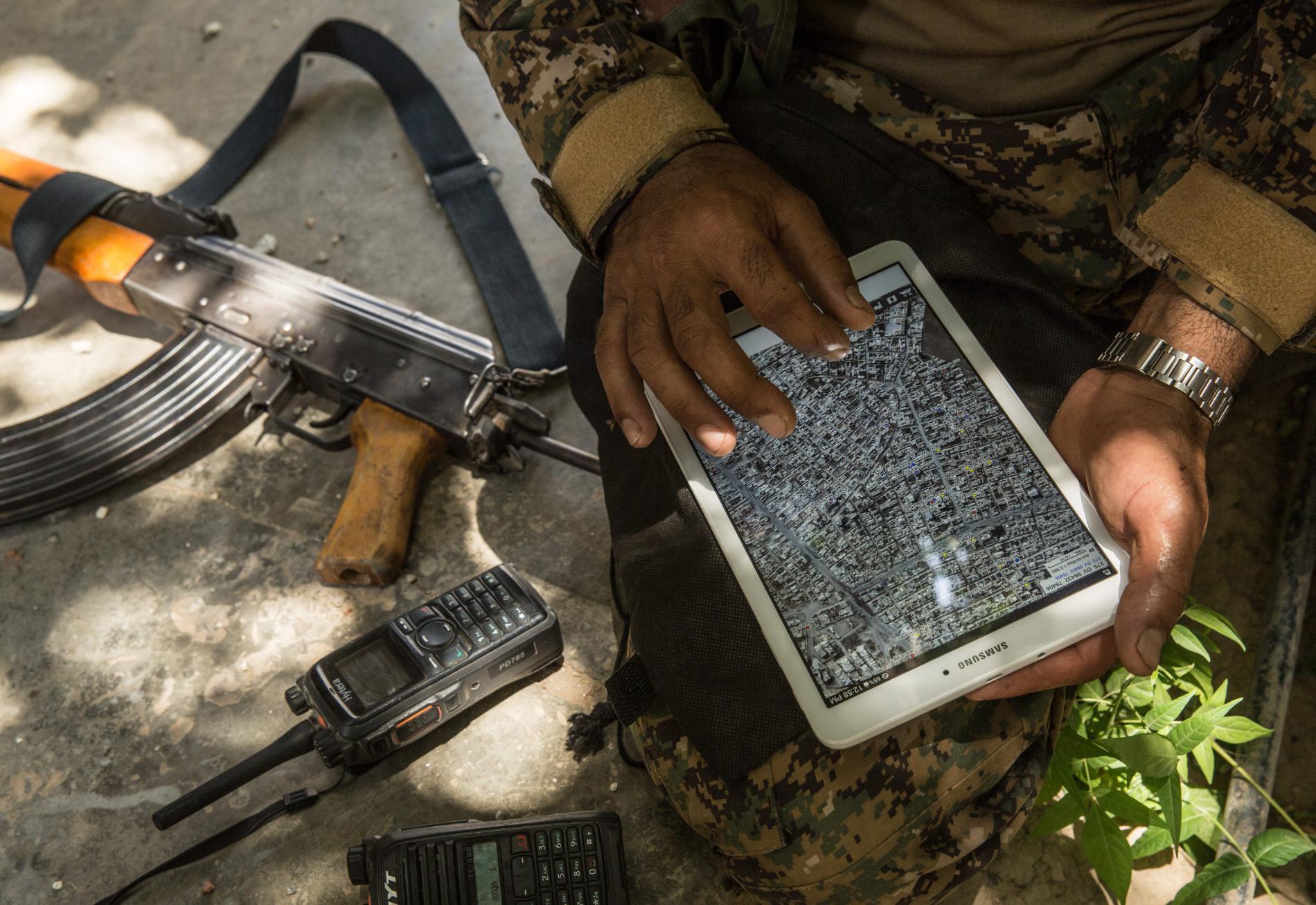 Un soldat kurde des FDS consulte les images prises par un drone sur une tablette, à Raqqa (Syrie), le 1er juillet 2017.