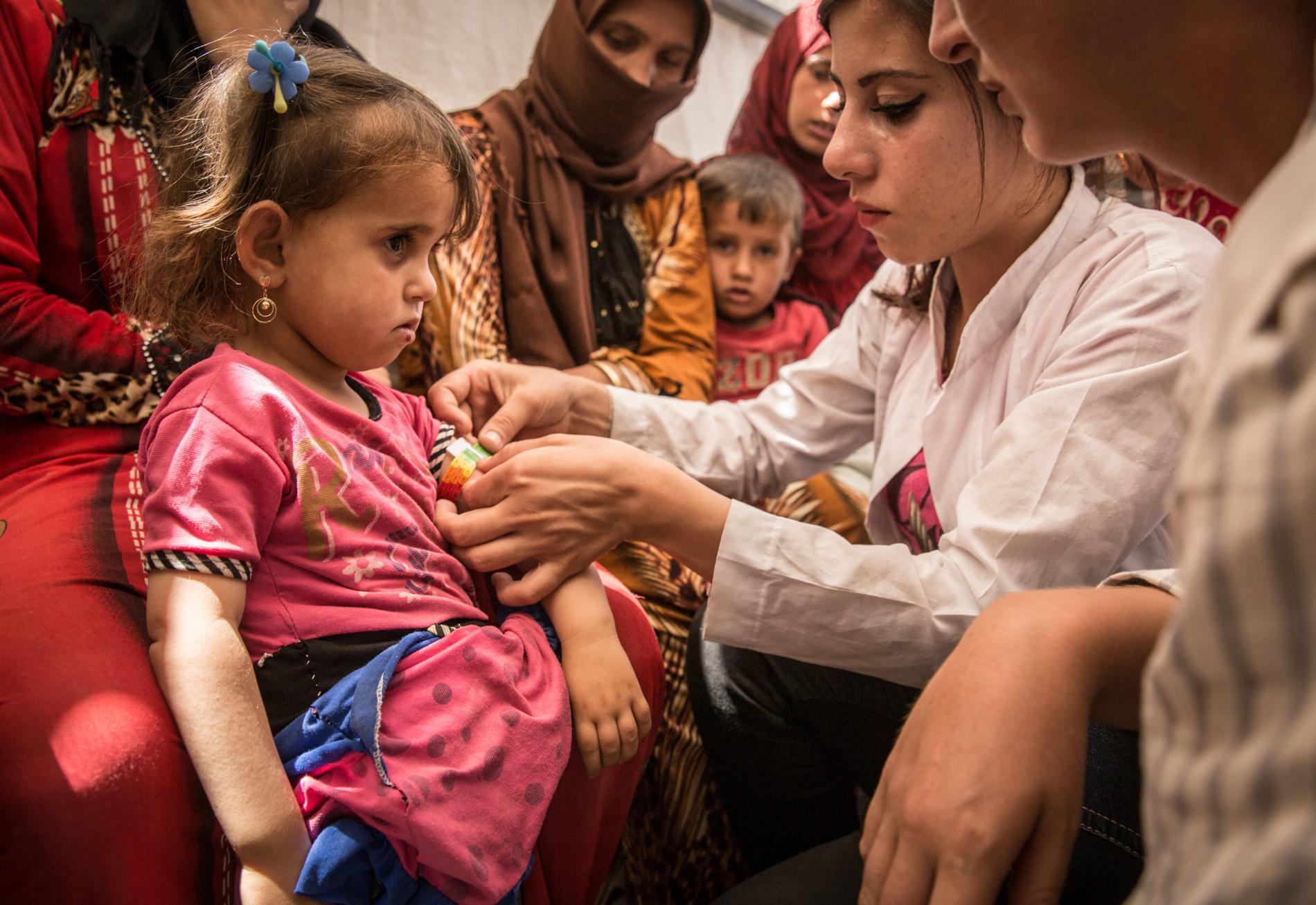 Dans le camp de réfugiés d\'Ain Issa (Syrie), une médecin de l\'ONG Médecins sans frontières ausculte une petite fille qui a fui Raqqa avec sa famille, le 8 juillet 2017.