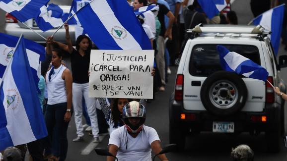 """Des manifestants anti-gouvernement forment une \""""chaîne humaine\"""", à Managua (Nicaragua), le 4 juillet 2018. Sur la pancarte : \""""Justice ! Prison pour Ortega ! Qu\'ils s\'en aillent !\"""""""