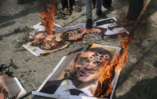 Des images d'Emmanuel Macron avec une empreinte dechaussureont été brûlées, à Gaza, dans les territoires palestiniens, le 30 octobre 2020. (SAID KHATIB / AFP)