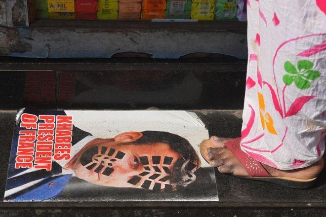 Une affiche présentant Emmanuel Macron avec une empreinte de chaussure sur le visage, à Bombay (Inde), le 30 octobre 2020. (INDRANIL MUKHERJEE / AFP)