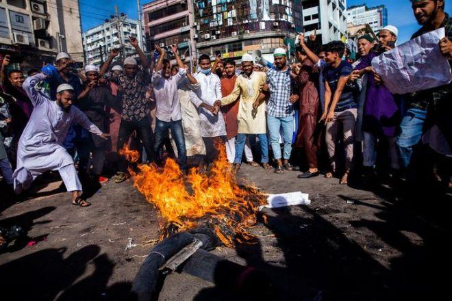 Des manifestants brûlent effigie d'Emmanuel Macron lors d'une manifestation à Dacca (Bangladesh), le 30 octobre 2020. (MUSHFIQUL ALAM / NURPHOTO / AFP)
