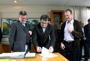 Deputado Assis do Couto e o presidente da associação de moradores, Renir 'Chico' Comunello observam a assinatura da ordem de serviço pelo prefeito Neto para avenida que ligará o São Cristóvão à PR-483