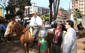 Alberi Agnoletto, hospedeiro da centelha, observa o acendimento da chama crioula pelo coordenador do evento, Amarildo Petry e prefeito Cantelmo Neto