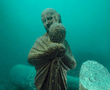 The statue of an Isis priest holding an Osiris-jar found on the sunken Island of Antirhodos in the great harbour of Alexandria. The statue from black granite is 1.22 meters high.