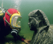A diver eye-to-eye with a sphinx made out of black granite. The face of the sphinx is believed to represent Ptolemy XII, father of the famous Cleopatra VII. The sphinx was found during excavations in the ancient harbour of Alexandria.