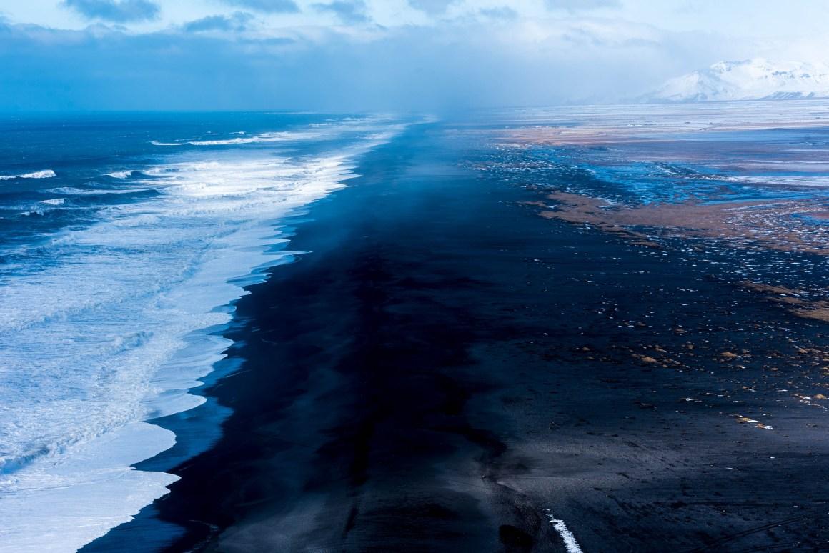Sable noir entre montagnes et océan