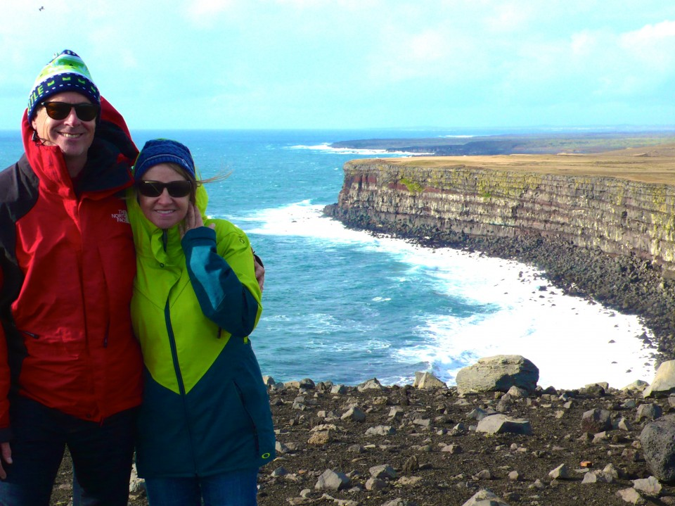 Doug and Debi with magnificent cliff behind them, Reykennes Peninsula