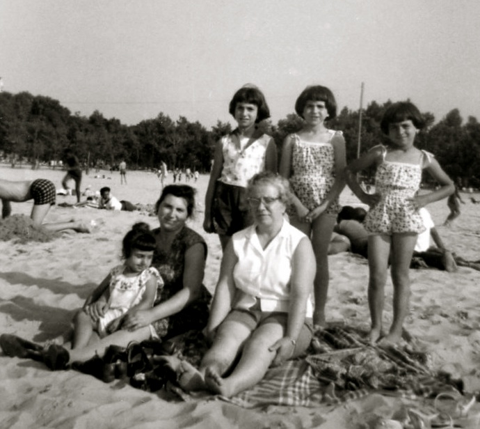 The summer before my birth, Miller Lake, Gary, Indiana.  Mom is holding Zina and my other three sisters stand in the second row.  My Aunt Maria, wearing a white blouse, is next to mom.  Mom is pregnant with me.  I wonder if a watermelon is sitting in an icebox nearby.