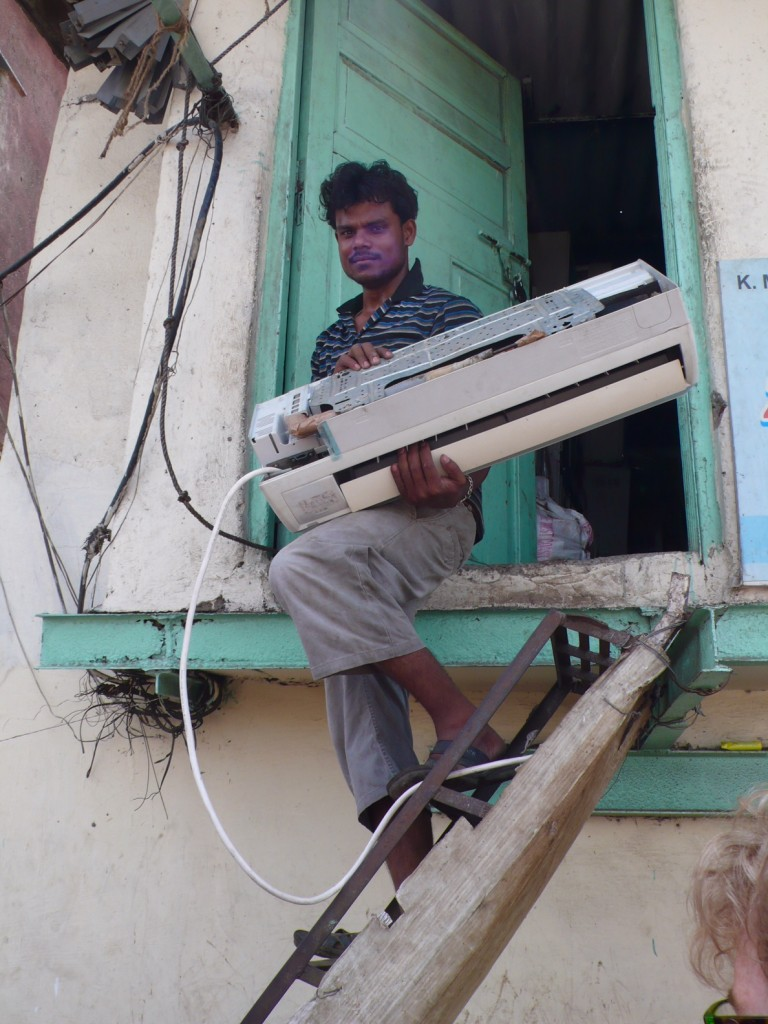 Man coming down from makeshift second story, carrying a broken Airconditioned, which will be reconfigured and working again, only to be resold without a warranty