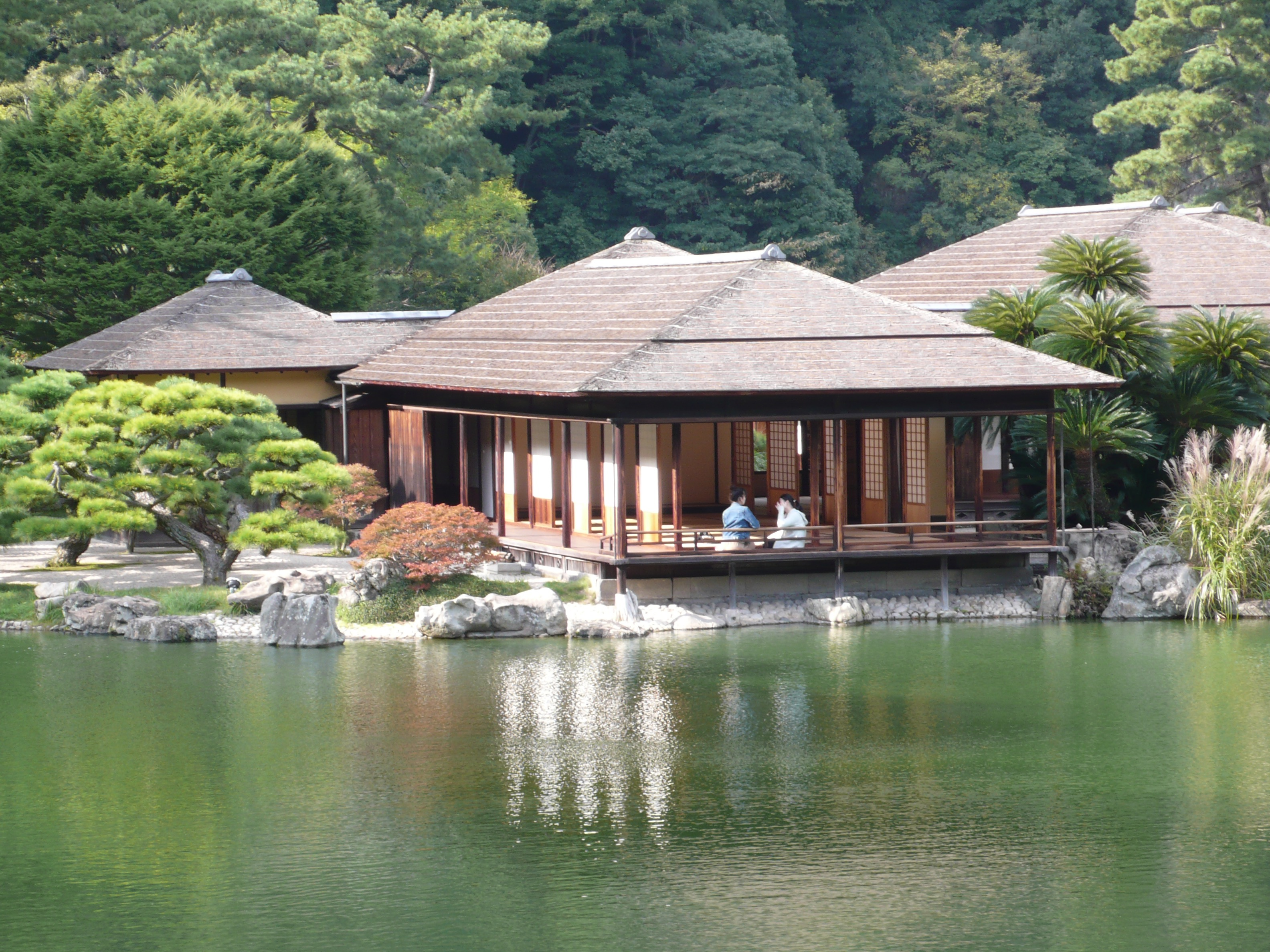 A tea house reflected in the water.  What I love about this tea house are the two people enjoying their tea.