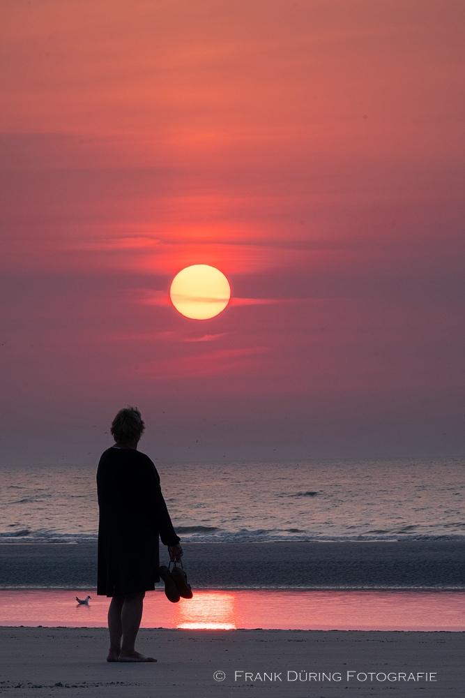 Frau in der Abendsonne am Strand bei Buren, Ameland, NL