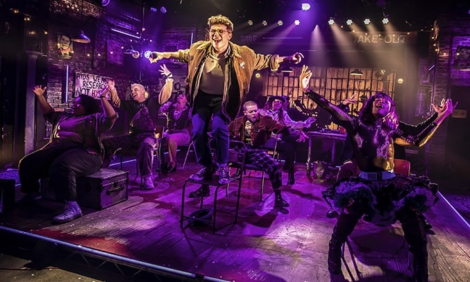 Blake Patrick Anderson (Mark) and the Company of RENT at Hope Mill Theatre.