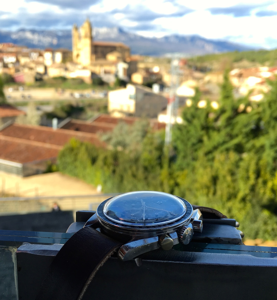 The Omega Speedmaster 145.012 against a backdrop of the town of Elciego