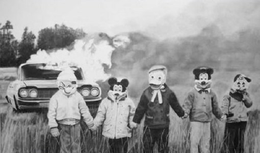 Burning car and children wearing masks