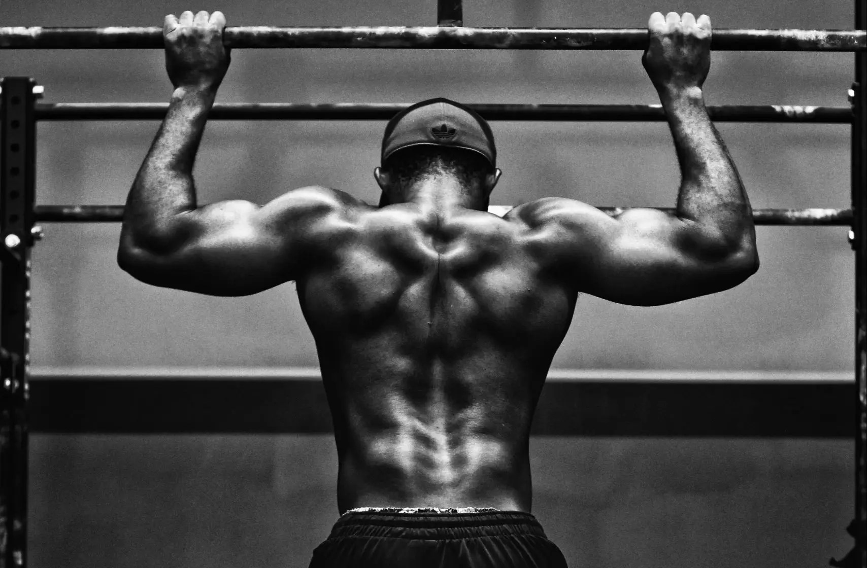 Man hanging on the bar as fitness goals and busting bodybuilding