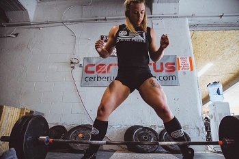 Bodybuilder women lift up weights as strength training for women